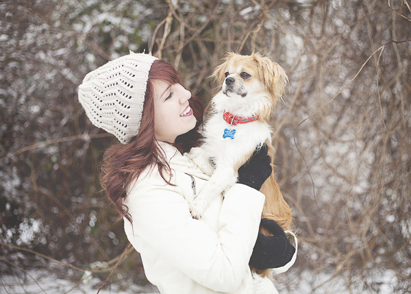 woman in white beanie holding small Pekingese mix, winter lifestyle dog photography