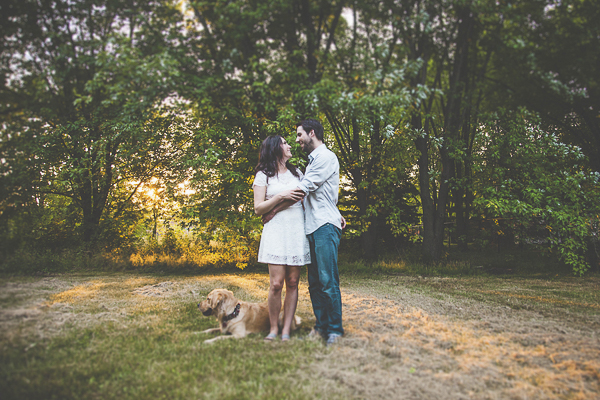 Dog lying on grass at edge of field, man woman embracing, engagement photos with dog