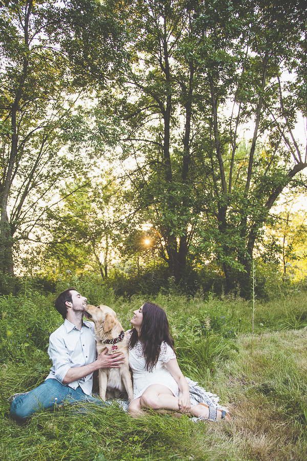 dog licking man's face during engagement session,