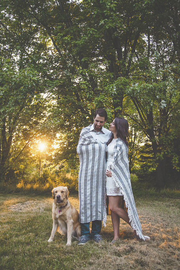 dog sitting next to humans wrapped in blanket, golden hour engagement pictures with Golden Retriever