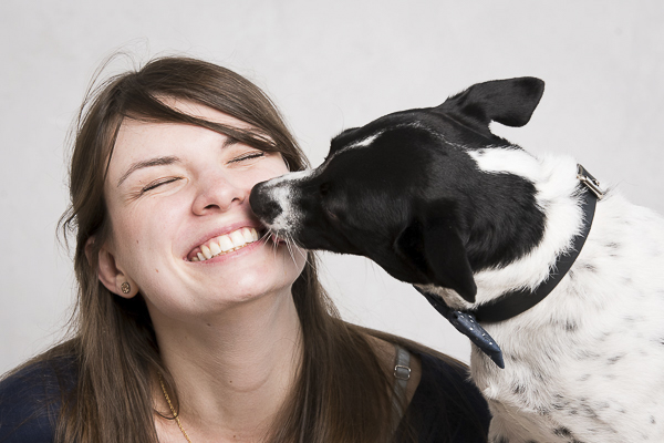 woman smiling, dog licking woman's face The Broke Dog