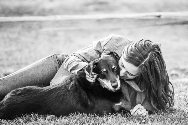 black dog lying on grass cuddling with woman