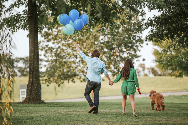man holding green, blue balloons, walking away with dog and wife