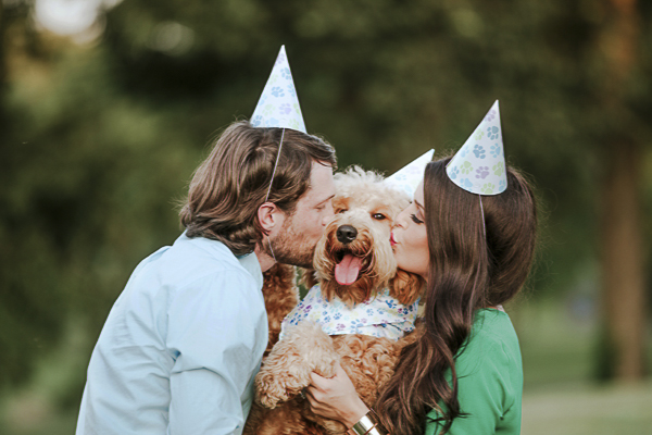 dog's birthday pawty, couple kissing dog, party hats with paw prints