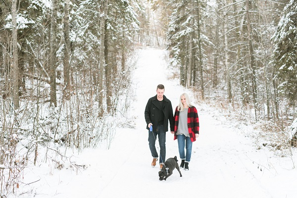couple walking dog in snowy woods