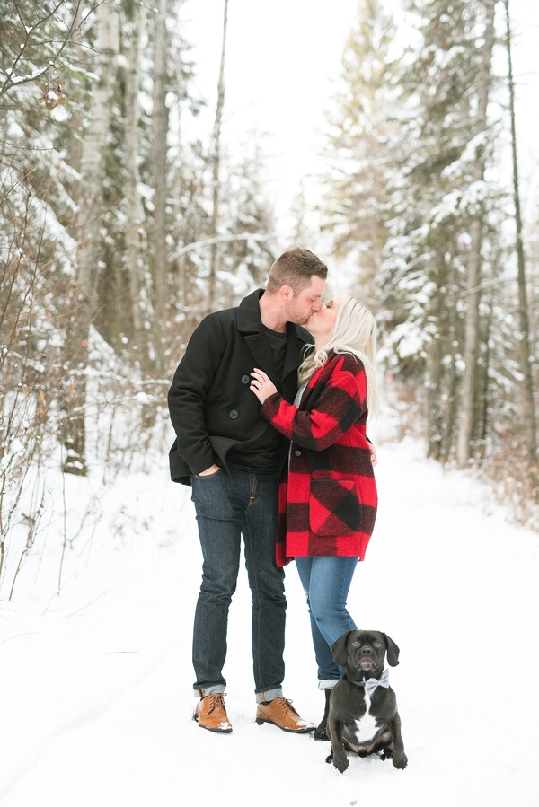black Puggle sitting next to couple on snowy day