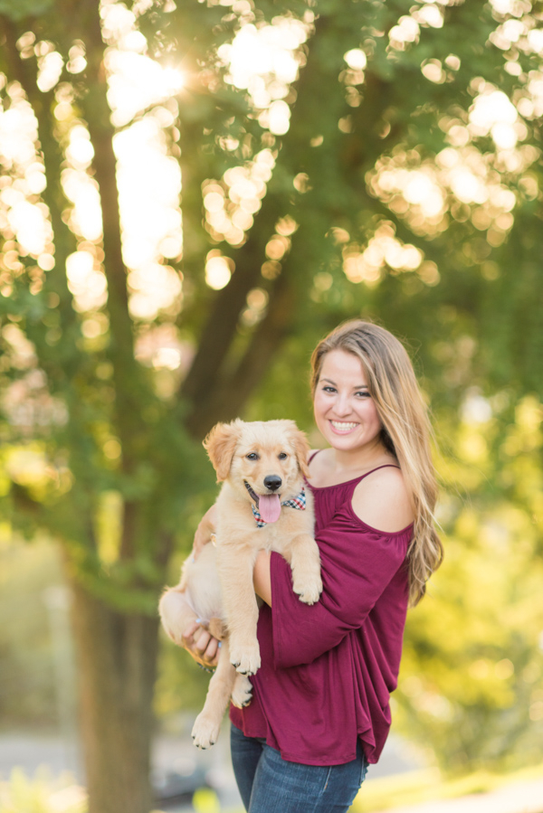 blond woman holding 3 month Golden Retriever puppy