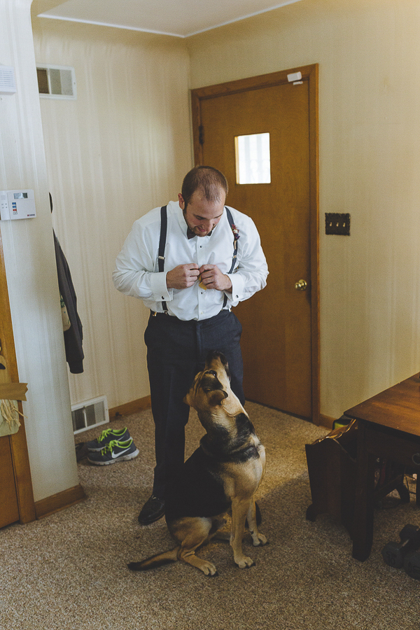 dog watching groom get ready for wedding