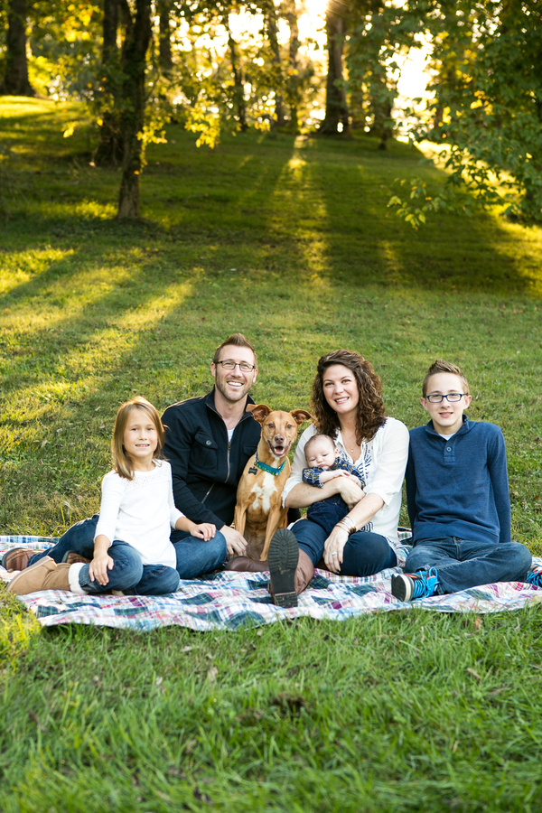 happy dog and family on blanket,