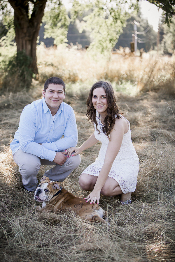 couple in field with English Bulldog pup