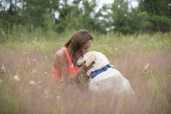 woman kissing Lab's head, human-dog bond