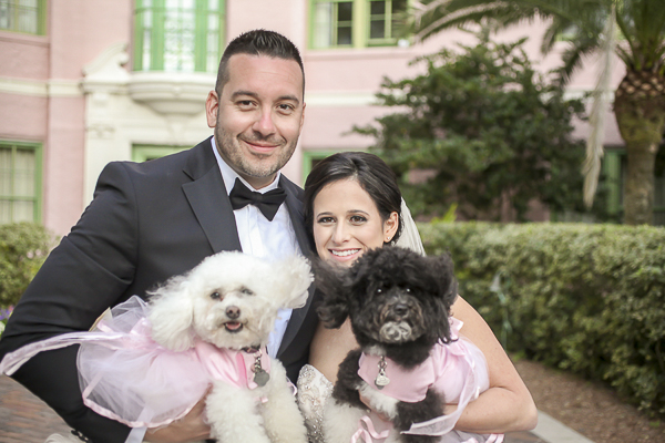groom holding white poodle, bride holding black and white poodle
