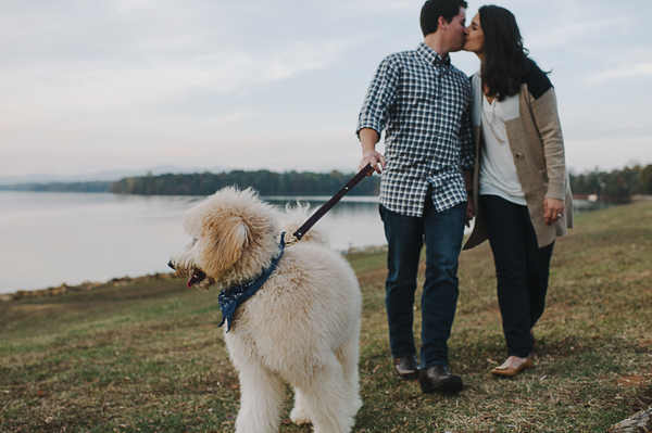 couple kissing while walking Golden Doodle by water