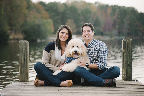 couple and dog sitting on lake dock