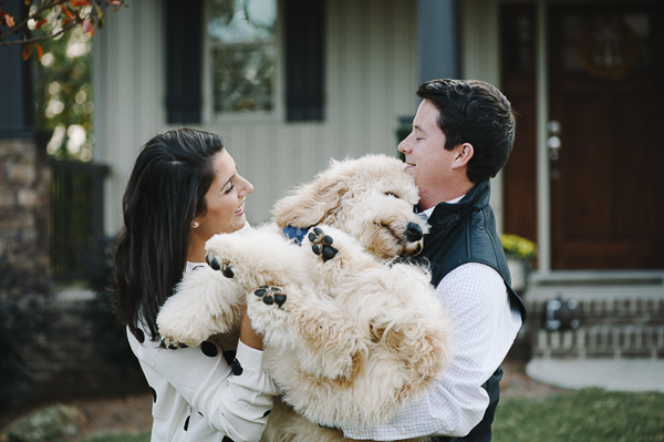 couple holding Golden Doodle like a baby, dogs are family