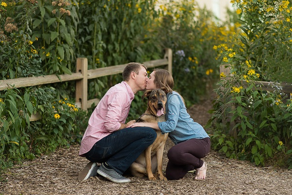 couple kissing over dog's head, on location engagement photos