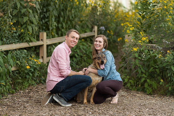 couple, dog on mulch trail, flowers in background, engagement pictures with dogs