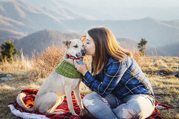 woman kissing blond shepherd mix on mountain, epic dog portraits