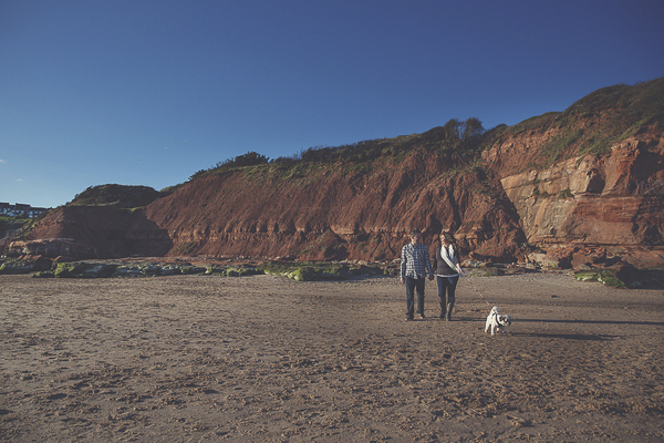 couple walking dog on beach, cliffs background, Jurassic Coast engagement pictures