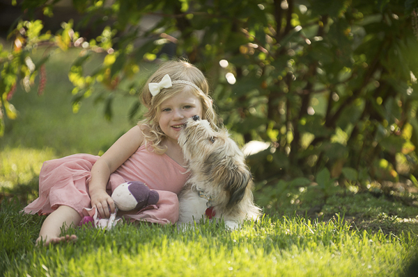 dog kissing little girl, bond between dogs and kids,