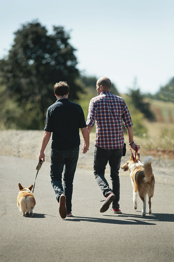 couple holding hands while walking dogs, engagement photography with dogs,