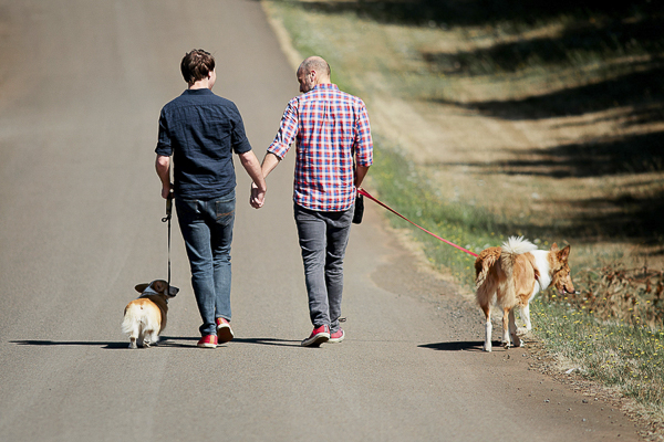 engaged couple walking dogs down the road