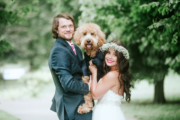bride and groom holding dog in tux, wedding dog