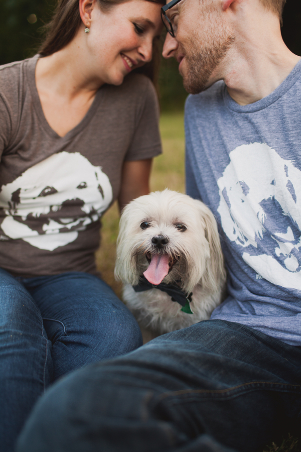 little dog sitting between engaged couple, couple wearing matching t shirts with dogs face, dog with Teddy Roosevelt mustache