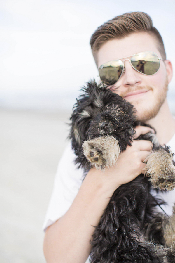 man holding black puppy , Schnoodle