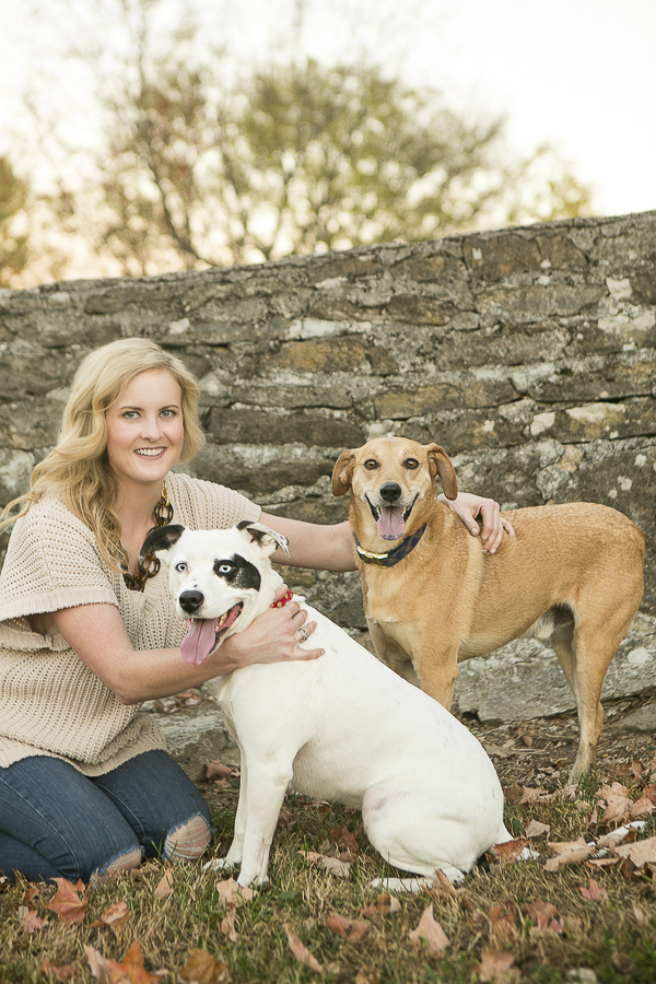 woman, Dalmatian/Pit mix, brown hound/lab mix in front of stone wall