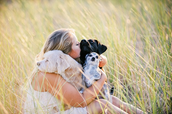 High school senior holding three dogs in the field