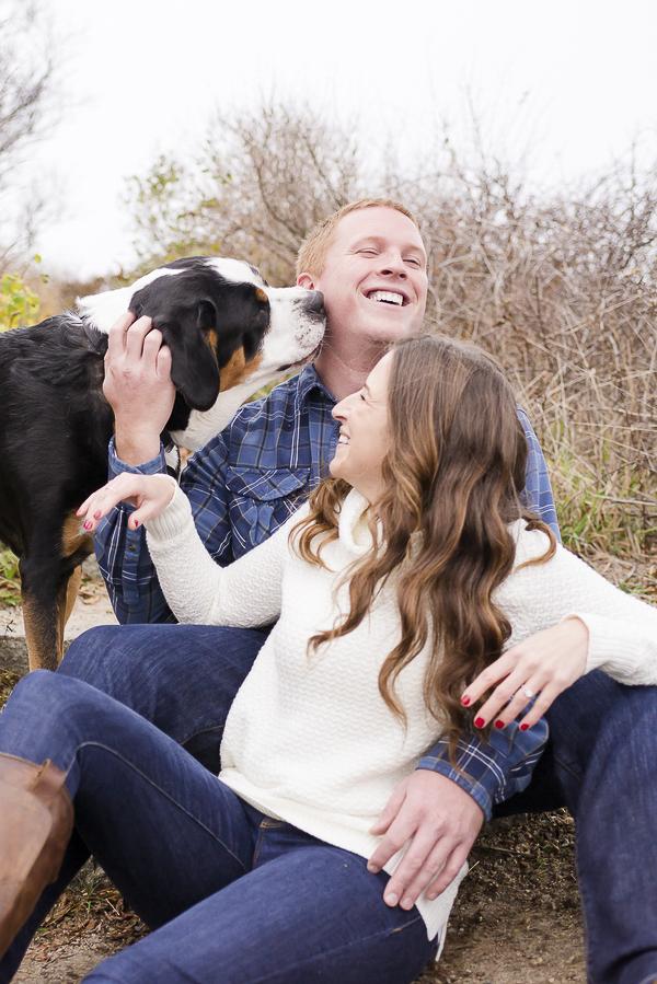 man laughing as big dog licks his cheek, engagement photos with a dog
