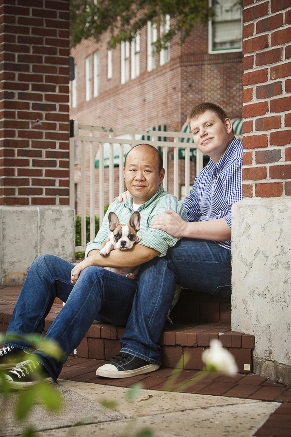 same sex couple sitting on steps with puppy, engagement portraits with French Bulldog puppy