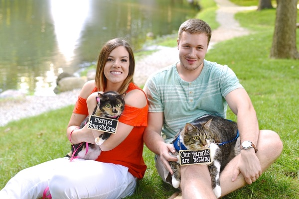 engaged couple holding their cats wearing save the date signs
