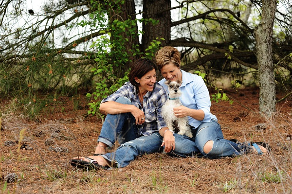 women sitting on pine needles with dog, relaxed engagement session