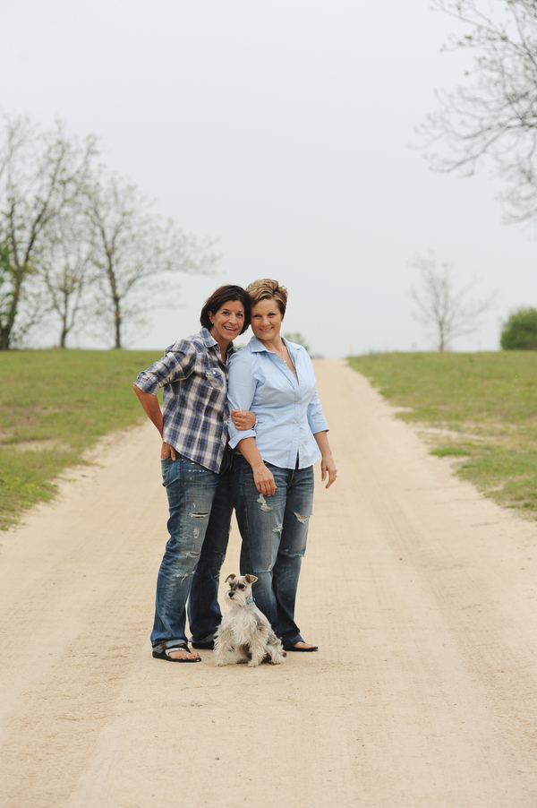 women and dog on dirt road, country engagement photos with Schnauzer