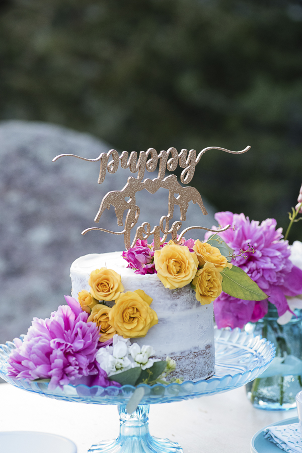 wedding cake with puppy love topper and flowers