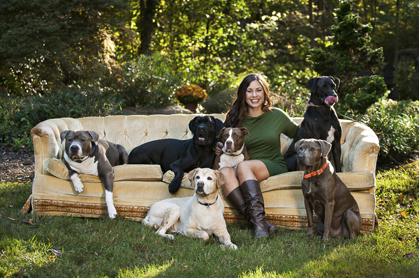 woman and six dogs sitting on sofa outside, lifestyle dog photography