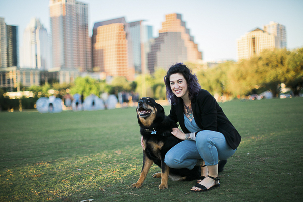 Shepherd mix, woman at park, cityscape in background