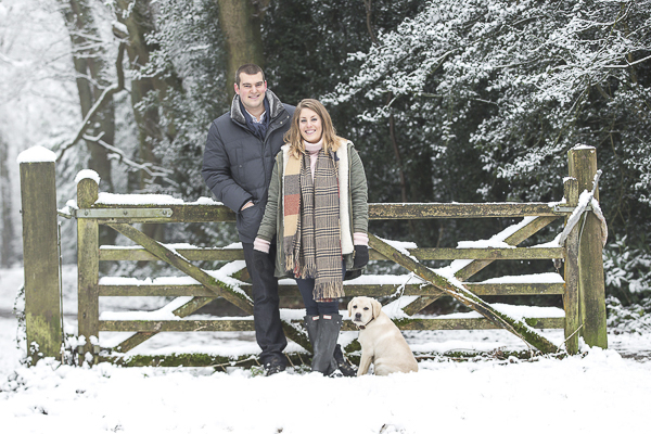 couple and puppy standing by rustic gate, winter engagement photo ideas