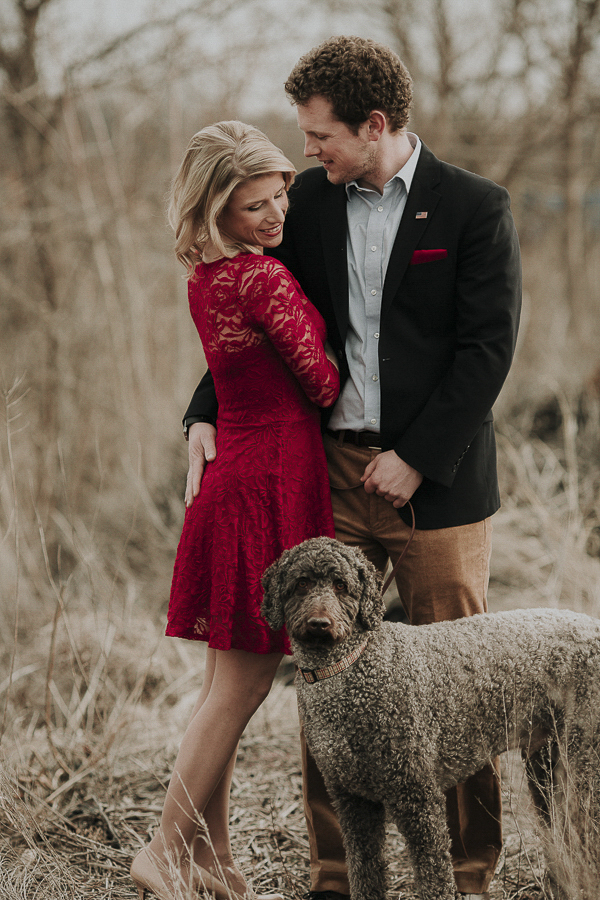 couple in field, winter engagement pictures with dog, Labradoodle