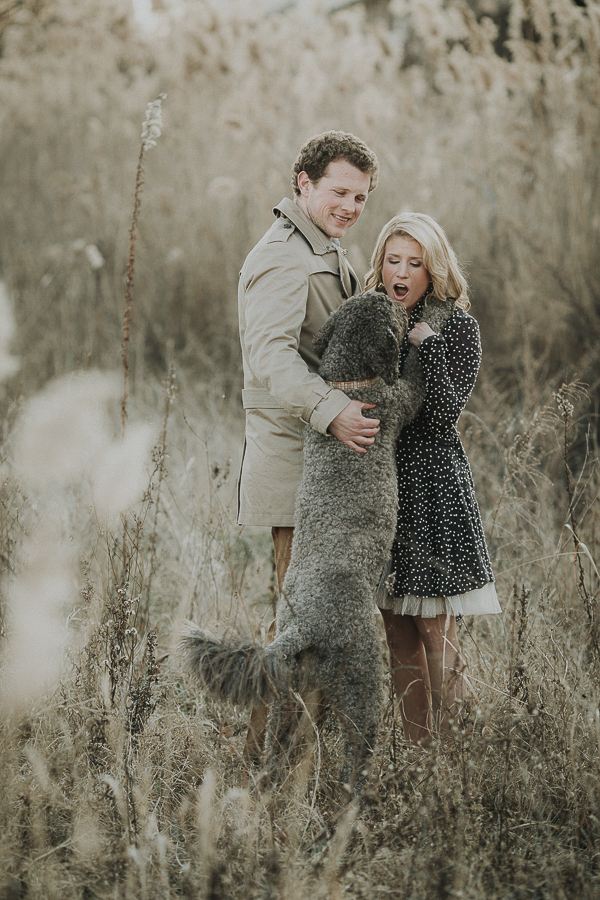 dog jumping up on woman during winter engagement photo session