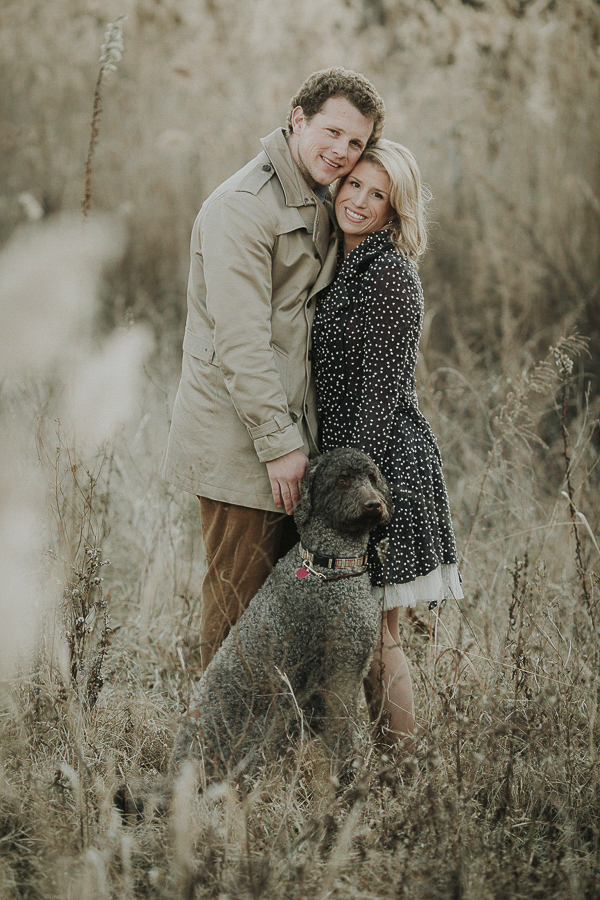winter engagement photos with Labradoodle, woman wearing cute black coat with white flecks