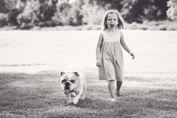 English Bulldog and little girl walking in park, lifestyle photography