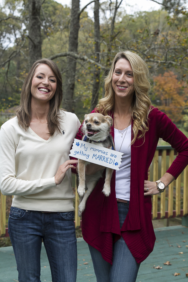 "engagement photos of dog and 2 women, dog wearing ""save the date sign"""