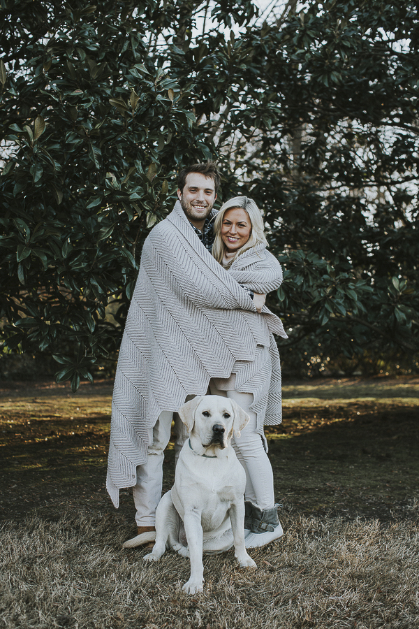 engaged couple wrapped in blanket, English Lab sitting in front of them
