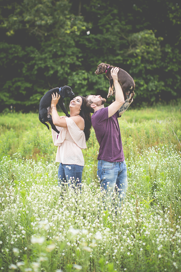 couple holding puppies in the air, on location family photos, SW Michigan