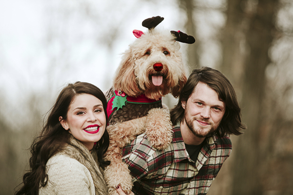 woman, dog wearing antlers and red nose, man, holiday photos with dog
