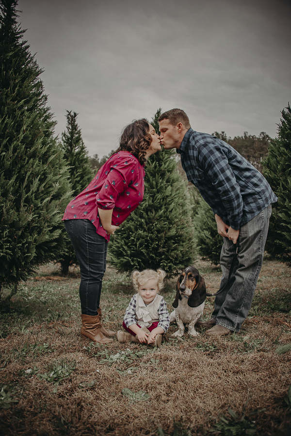 Parents kissing above little kid and Basset Hound sitting on the ground, Holiday photo ideas