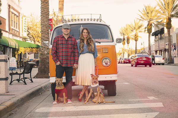 couple and dogs in front of orange VW van,